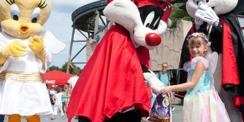 Looney Tunes characters dressed in Halloween costumes with small girl