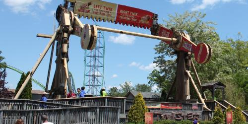 Twister, a long ride flipping guests head over heels in front of Kindga Ka coaster and a blue sky