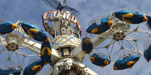 close-up of blue Condor cars rotating high in the sky with guests