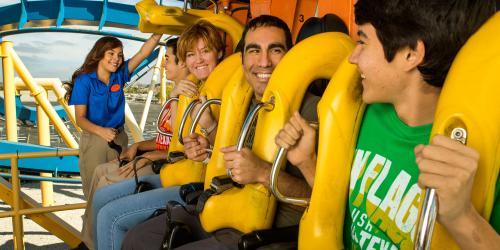 Team member checking seatbelts on roller coaster