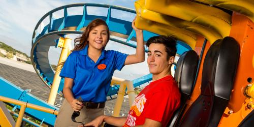 Employee helping guest onto rollercoaster