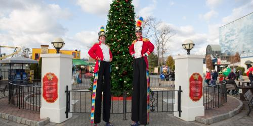 toy soldier stilt walkers in front of christmas tree