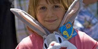 Small child smiling and holding a Bugs Bunny stuffed animal