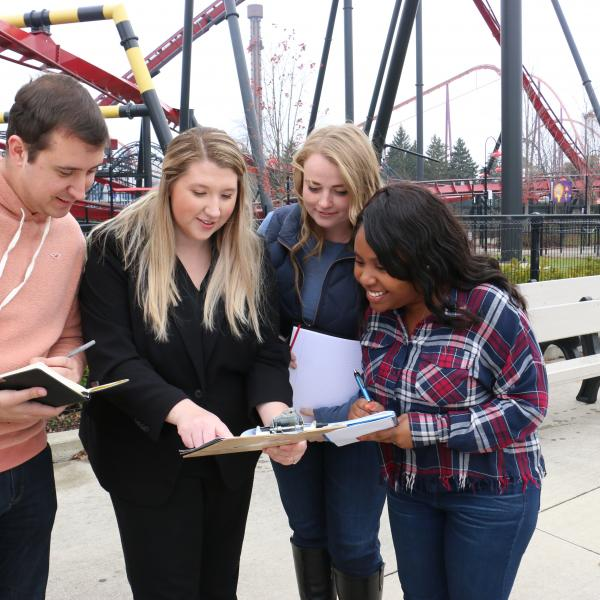 Students in front of Rollercoaster with teacher and clipboards