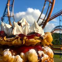 Fresh Funnel Cake with strawberries, chocolate syrup, vanilla ice cream topped with whipped cream.