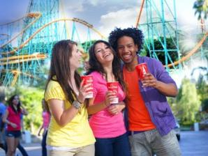 Three teenagers walking in the park sipping a soda with roller coaster in background