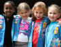 group of girl scouts in vests posing together