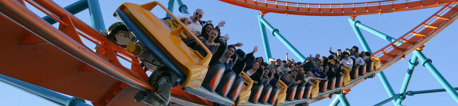Guests riding steel coasters at Six Flags with hands in the air