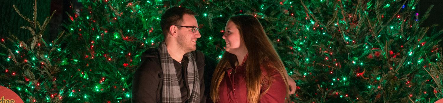 A couple cuddles under holiday lights for a romantic moment.