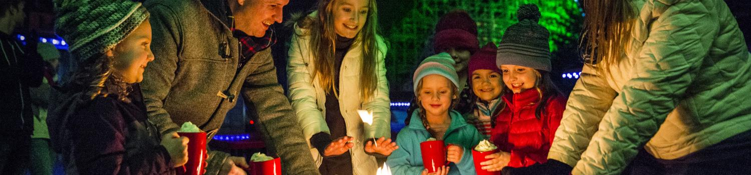 Family warming by the fire at Six Flags Holiday in the Park