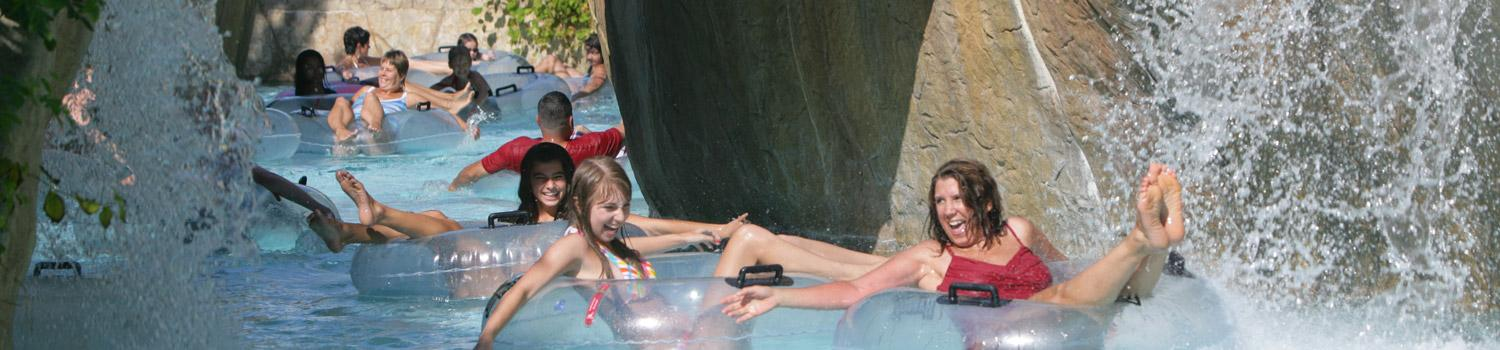 Smiling guests floating in inner tubes at Adventure River at Six Flags New England Hurricane Harbor