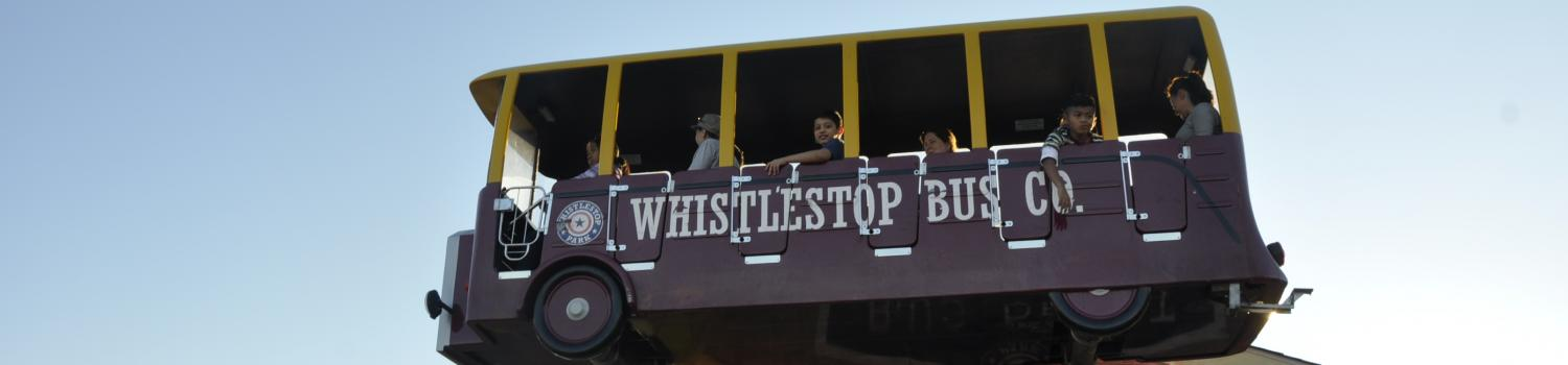 Children riding a bus themed ride in Whistlestop