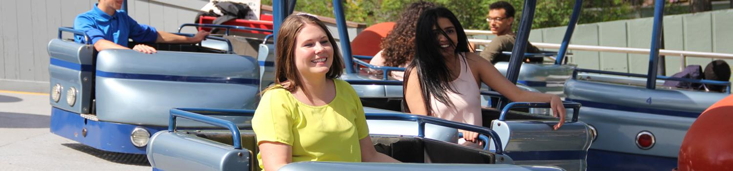 Teen girls smiling while riding Fiddlers Fling