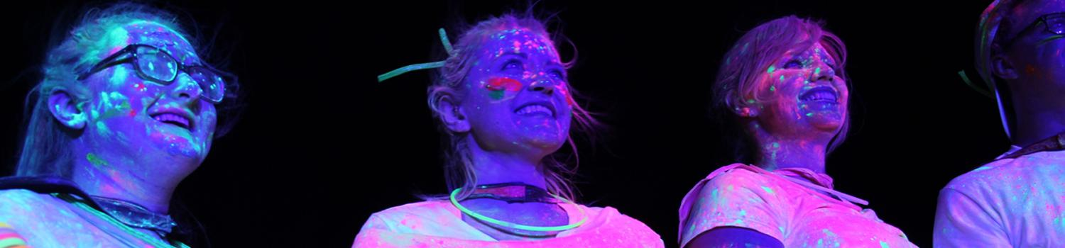 guests covered in glow powder during superhero glow run