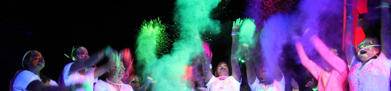 guests throwing glow powder in air during superhero glow run