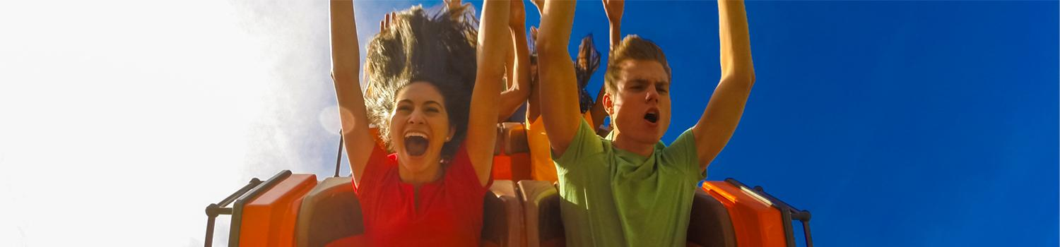 Smiling people riding a coaster.