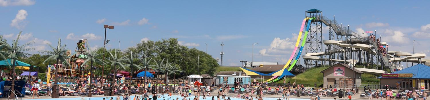 park vista shot of waterslides and swimmers in wavepool with bright blue sky and clouds
