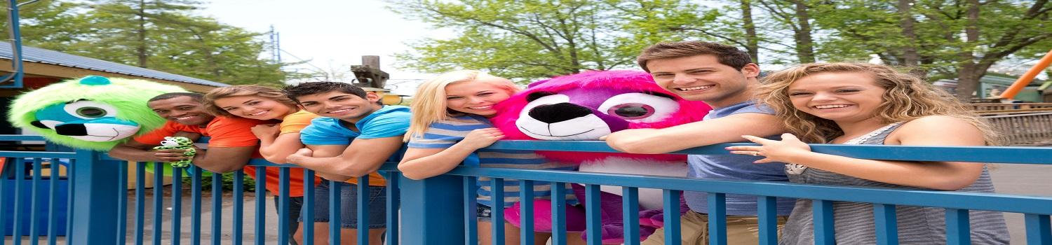 smiling teenagers leaning over a rail while some are holding stuffed animals.