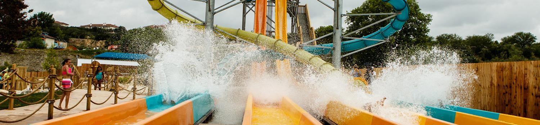 Four guests sliding into a bit splash on the 4 slides of Bahama Blaster