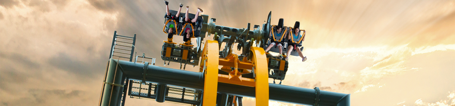 View of BATMAN: The Ride rotating over the top of a turn with guests