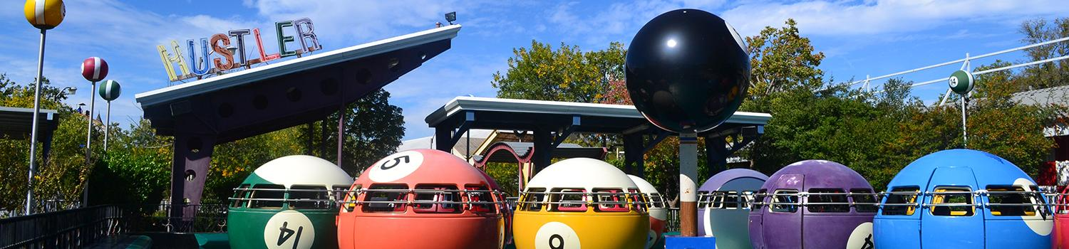 Guests riding inside billiard ball ride vehicles and spinning