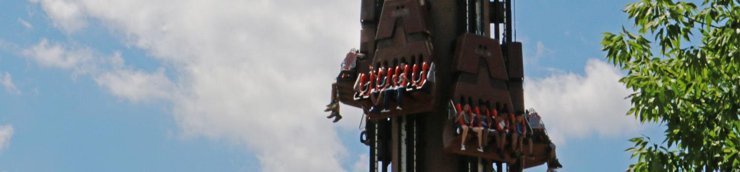 Giant Drop cars loaded with riders at the top
