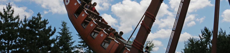 side view of River Rocker full of guests swinging midair
