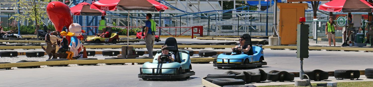 Riders in blue karts racing down the track of Winner's Circle Go Karts