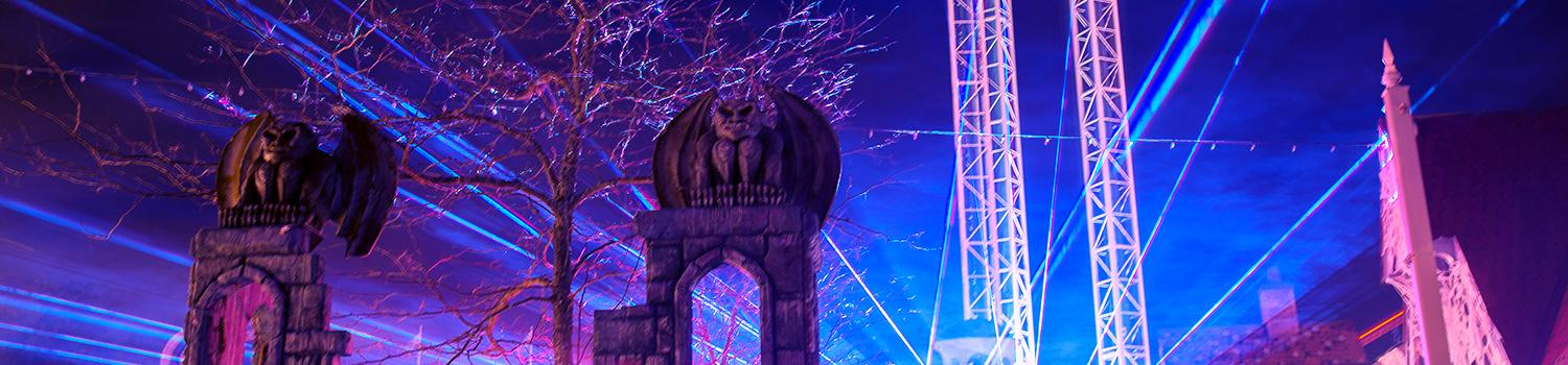 Lasers shine brightly over top two stone gargoyles