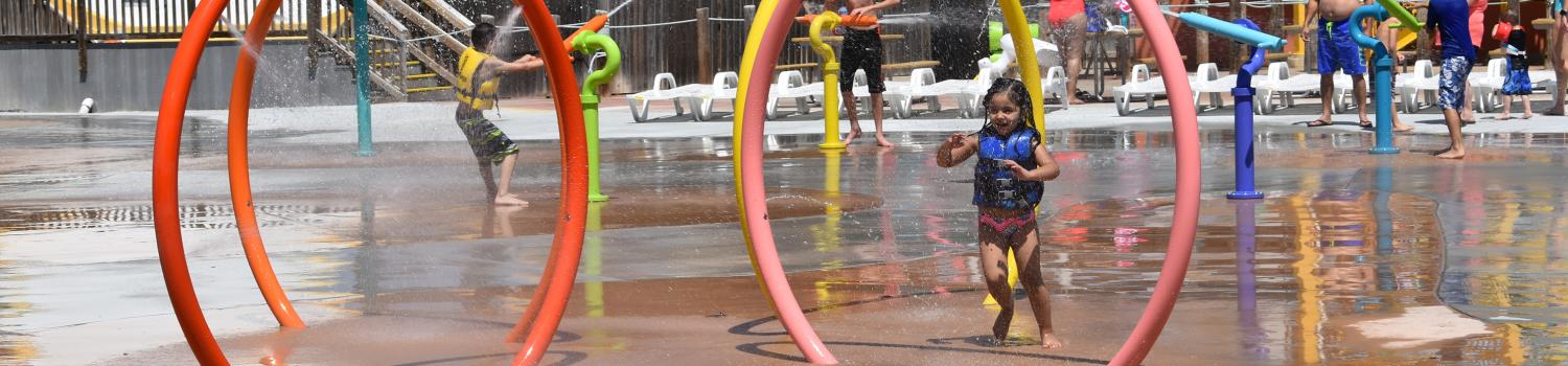 A little girl playing at Splashwater Beach at Six Flags Hurricane Harbor