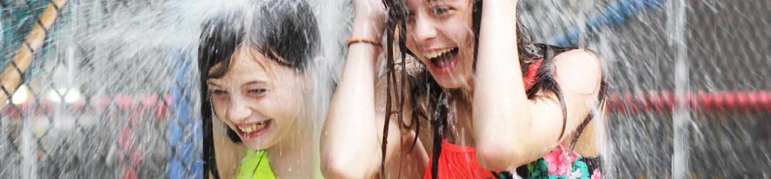 Girls getting drenched by water in White Water Bay at the Lodge.