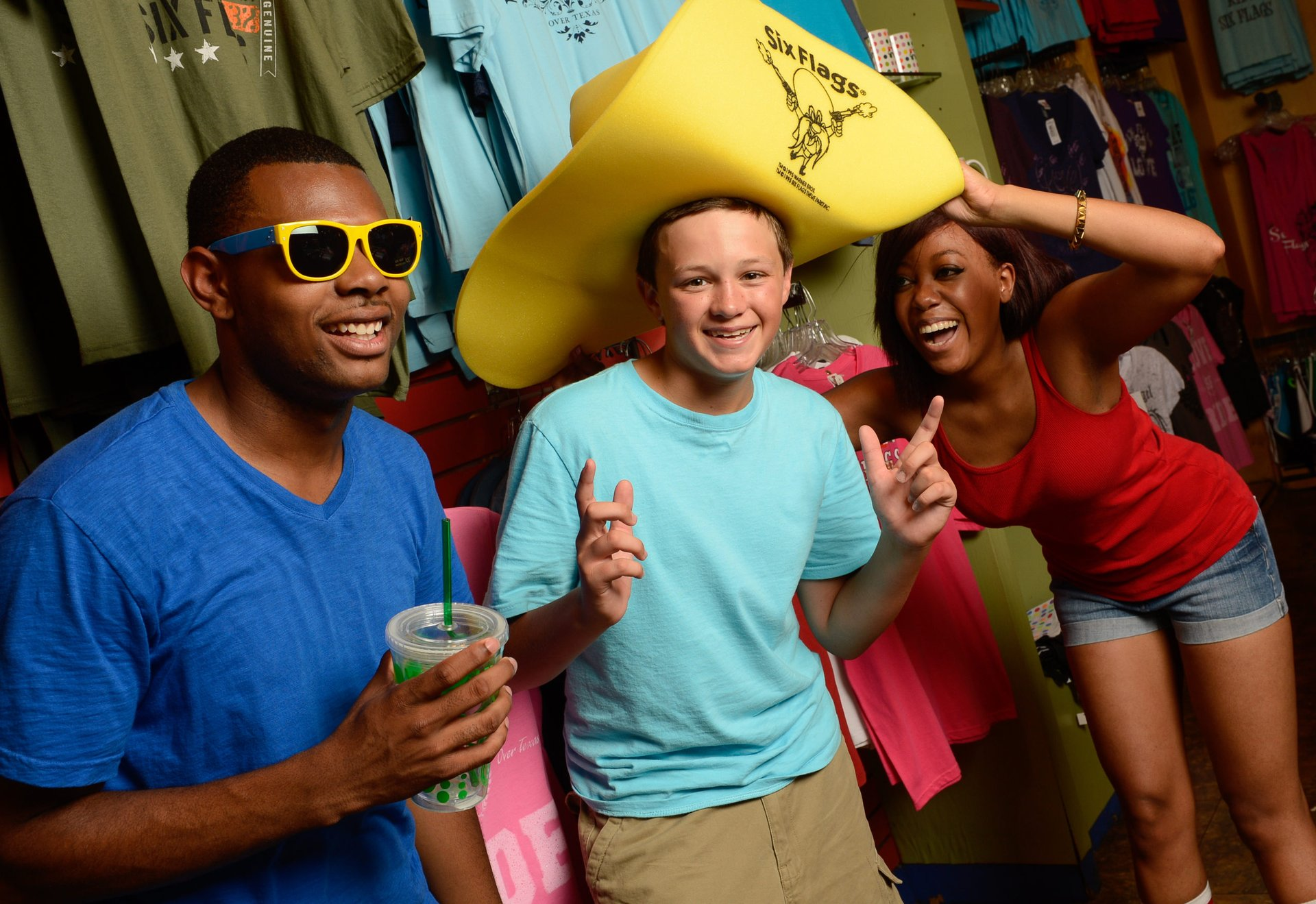 Three people smiling at the camera while shopping at a Six Flags theme park